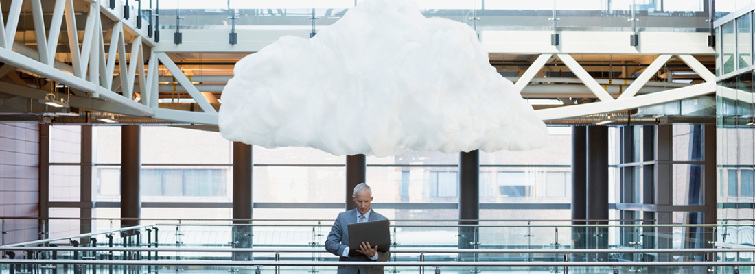 Man with laptop with cloud overhead